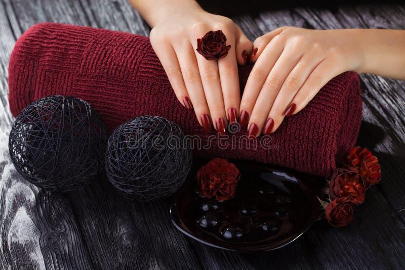 Tratamento de mãos vermelho com flores cor-de-rosa Termas imagens de stock royalty free