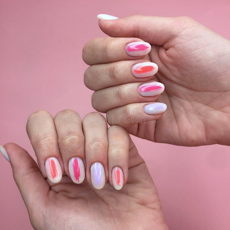 Tratamento de m?os de cores diferentes em pregos Tratamento de mãos fêmea na mão no fundo cor-de-rosa foto de stock
