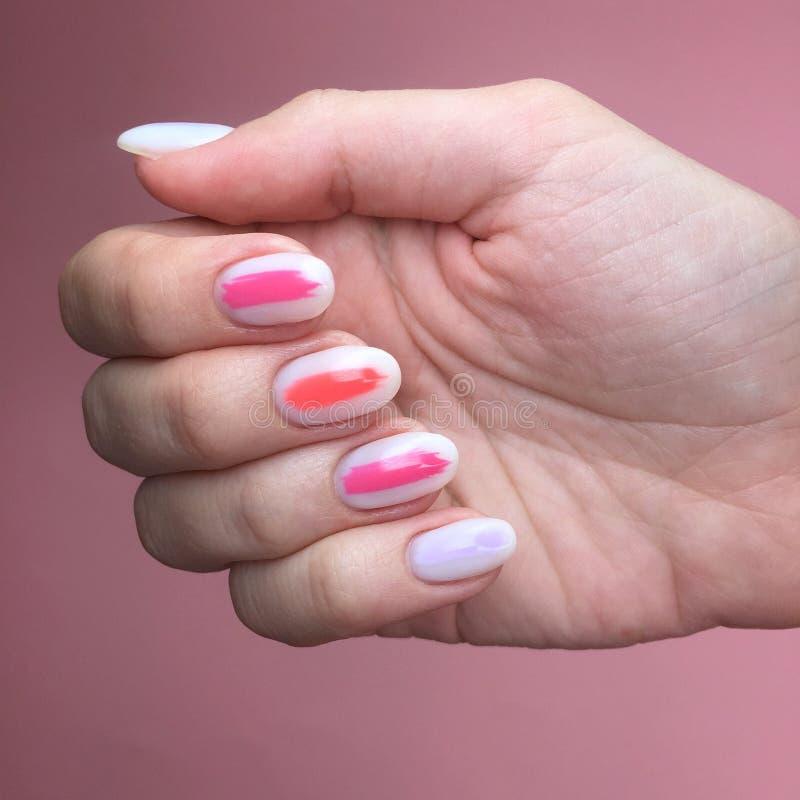 Tratamento de m?os de cores diferentes em pregos Tratamento de mãos fêmea na mão no fundo cor-de-rosa imagens de stock royalty free