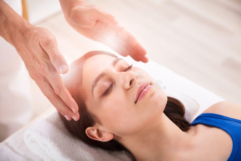 Tratamento de Performing Reiki Healing do terapeuta na mulher imagens de stock