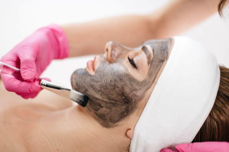 Tratamento do laser de Fraxel Obtenção pronto O esteticista está aplicando com a escova a máscara preta na cara do encantamento fotos de stock royalty free