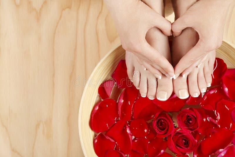 Tratamento dos termas do tratamento de mãos do pedicure com fundo da madeira das rosas vermelhas fotos de stock royalty free