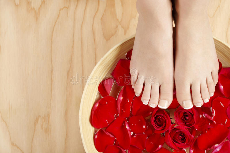 Tratamento francês natural dos termas do pedicure com fundo da madeira das rosas vermelhas fotografia de stock