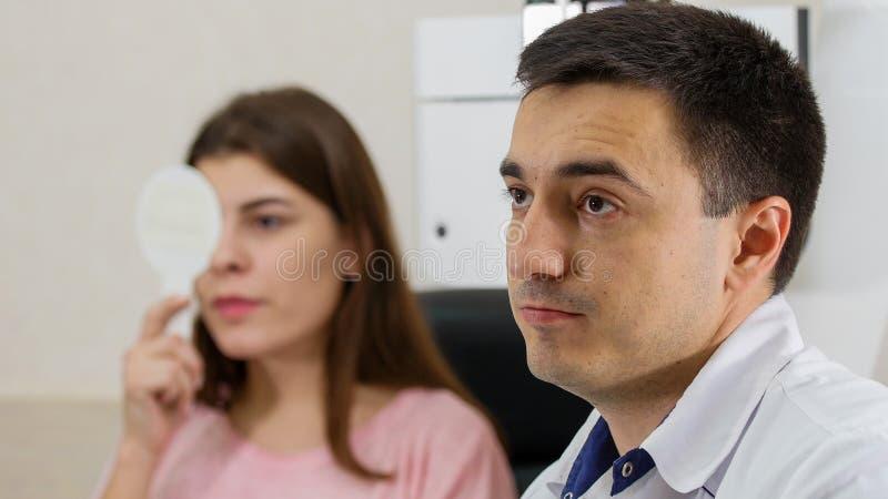 Tratamento oftalmológico - jovem mulher a verificar a sua acuidade visual fechando o olho com um escudo - um médico a observar fotografia de stock royalty free