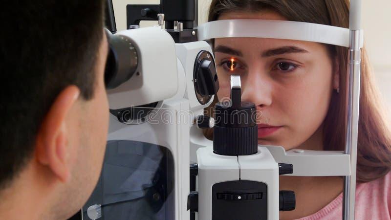 Tratamento oftalmológico - uma jovem com lábios cor-de-rosa a verificar a sua acuidade visual - reação do aluno à luz foto de stock