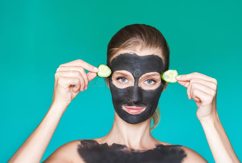 Tratamentos da beleza Uma jovem mulher aplica uma máscara preta, um creme em sua cara com seu ascendente próximo das mãos, pepino fotografia de stock