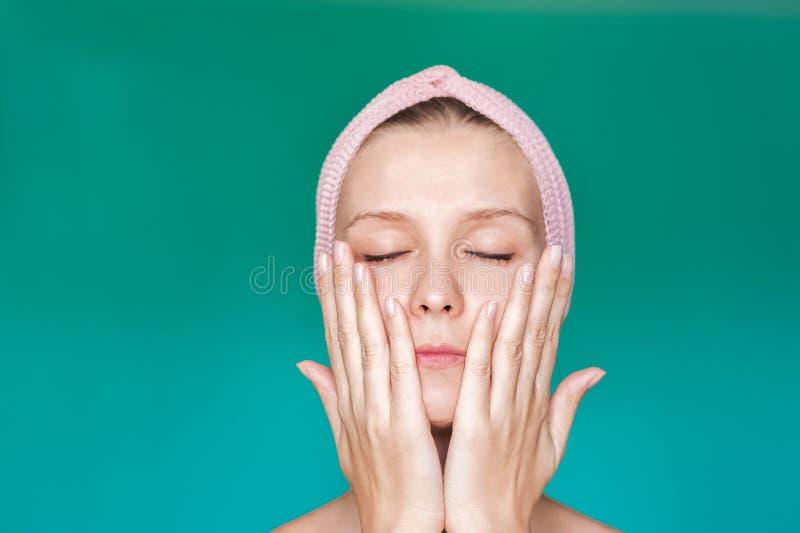 Tratamentos da beleza Uma jovem mulher está aplicando uma máscara, um creme em sua cara com suas mãos perto acima, lavando-se com foto de stock royalty free