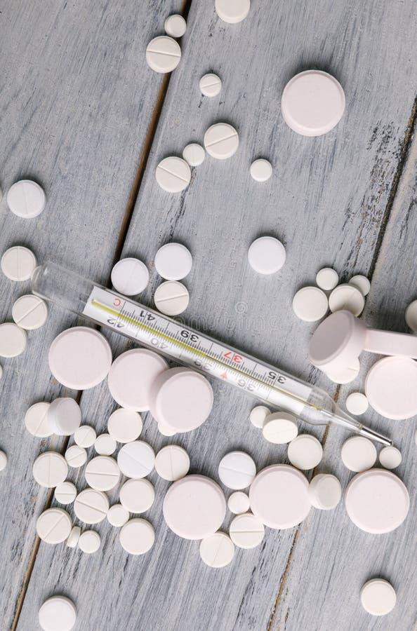 Tratamiento de fríos y de la gripe Diversas medicinas, un termómetro, esprayes de una nariz sofocante Copie el espacio Endecha pl foto de archivo