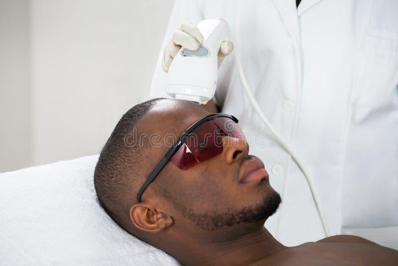 Tratamiento de Giving Laser Epilation del terapeuta en hombre joven fotos de archivo libres de regalías