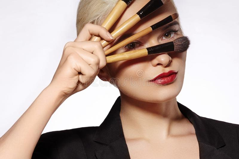 Tratamiento de la belleza Muchacha con los cepillos del maquillaje La moda compensa a la mujer makeover Artista de maquillaje App imagen de archivo libre de regalías