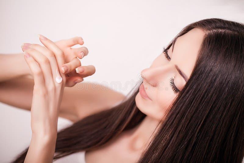 Tratamiento de la cara Mujer en salón de belleza Aplicación de la crema cosmética Una mujer joven hermosa que aplica la crema hid foto de archivo