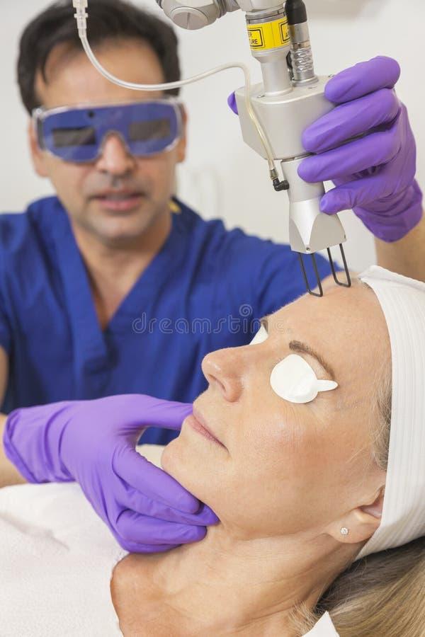 Tratamiento de la piel del doctor y del laser en mujer mayor foto de archivo libre de regalías