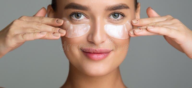 Tratamiento de la piel del ojo Mujer que se aplica debajo de remiendos del ojo foto de archivo libre de regalías