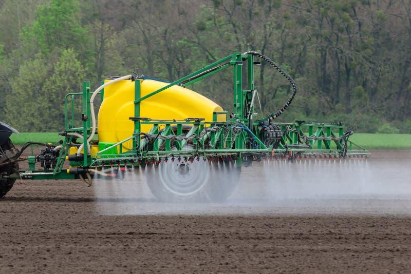 Tratamiento de las cosechas de la primavera con las sustancias qu?micas usando un tractor imagen de archivo libre de regalías