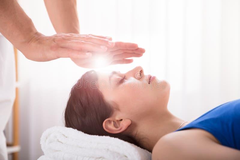 Tratamiento de Performing Reiki Healing del terapeuta en mujer fotos de archivo