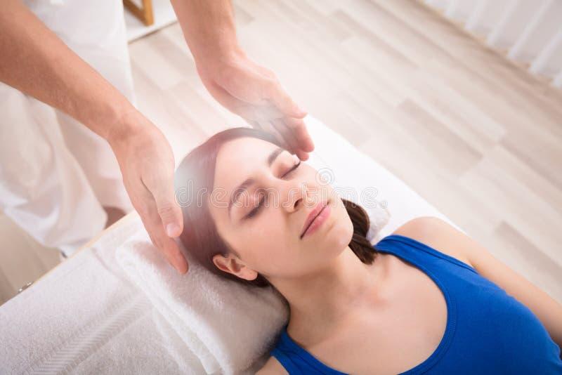 Tratamiento de Performing Reiki Healing del terapeuta en mujer foto de archivo libre de regalías