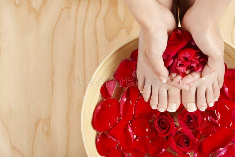 Tratamiento del balneario de la manicura de la pedicura con el fondo de madera de rosas rojas fotos de archivo libres de regalías