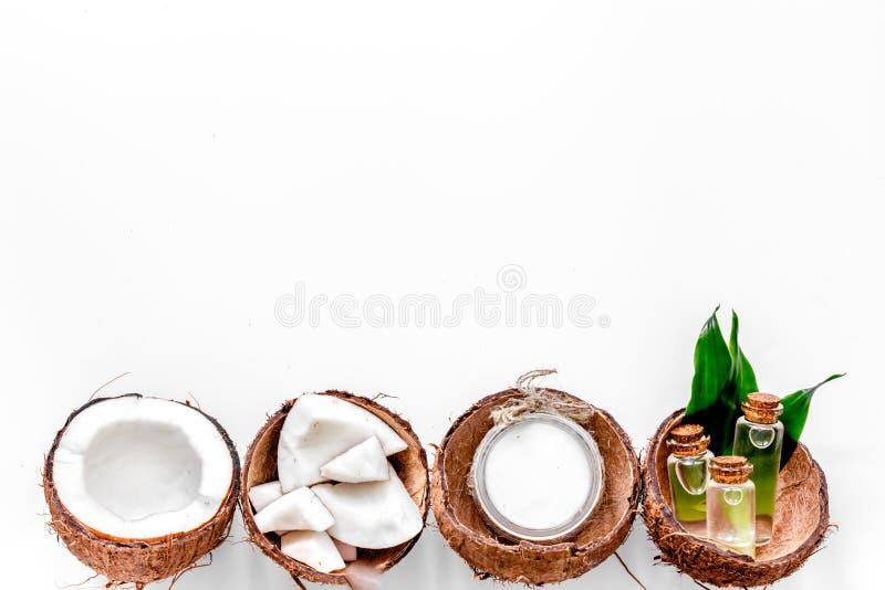 Tratamiento del cuerpo Aceite y loción de coco en el copyspace blanco de la opinión superior del fondo fotografía de archivo
