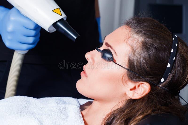 Tratamiento del laser de la cara de la mujer imágenes de archivo libres de regalías