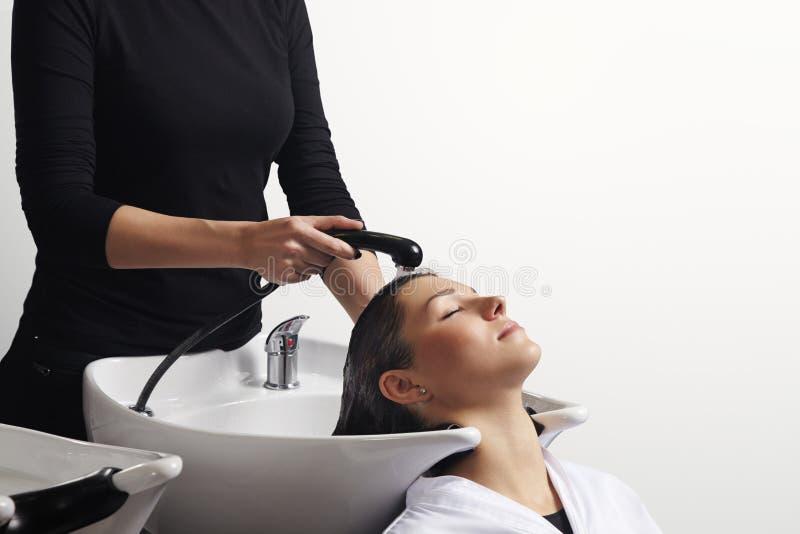 Tratamiento del pelo en el salón, pelo del ` s del cliente del peluquero que se lava foto de archivo