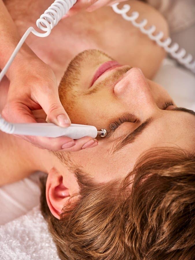 Tratamiento masculino facial de la cara del estímulo galvánico imagenes de archivo