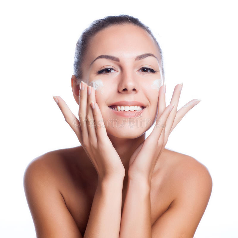 Tratamiento poner crema cosmético de aplicación modelo hermoso en su cara en blanco foto de archivo libre de regalías