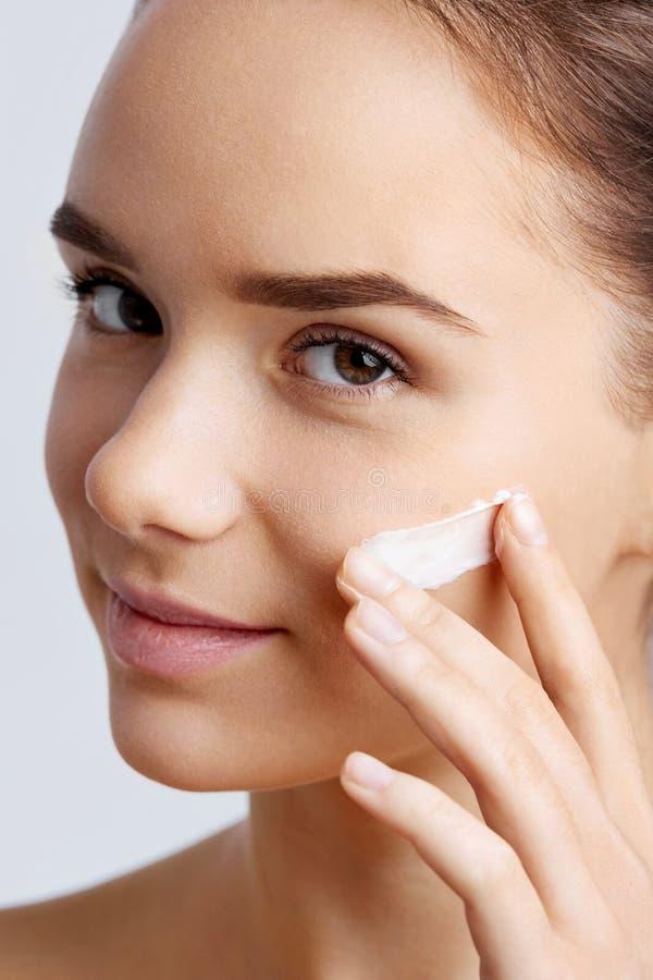 Tratamiento poner crema cosmético de aplicación modelo hermoso en su cara imagen de archivo libre de regalías