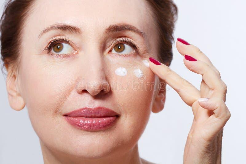 Tratamiento poner crema cosmético de aplicación modelo de la Edad Media hermosa en su cara aislada en blanco menopausia Wrinkl ma imagenes de archivo