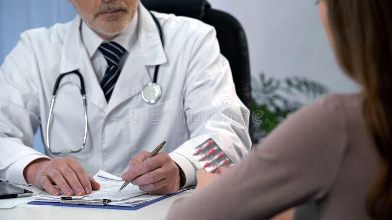Tratamiento que prescribe del médico de cabecera y píldoras del donante al paciente, atención sanitaria fotografía de archivo libre de regalías