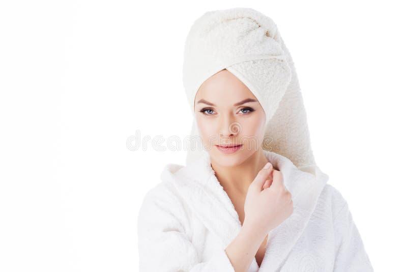 Tratamientos de la belleza después del baño Retrato de una mujer hermosa joven en un traje de Terry y con una toalla en su cabeza fotos de archivo