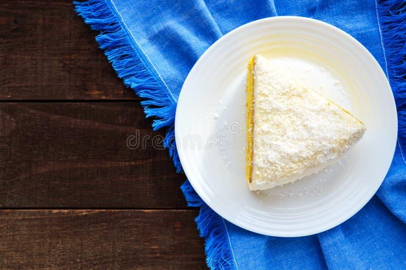 Trate la torta de esponja con suavidad con capa cremosa del plátano, asperje el coco en el top imágenes de archivo libres de regalías