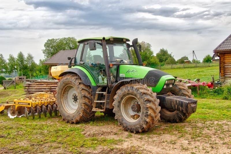 Trator agrícola com o arado de arrasto na vila do verão foto de stock royalty free