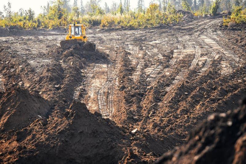 Trator buldozer retira a camada superior da floresta fértil sobre a superfície do solo, erva, local de colheita para a mina abert imagens de stock