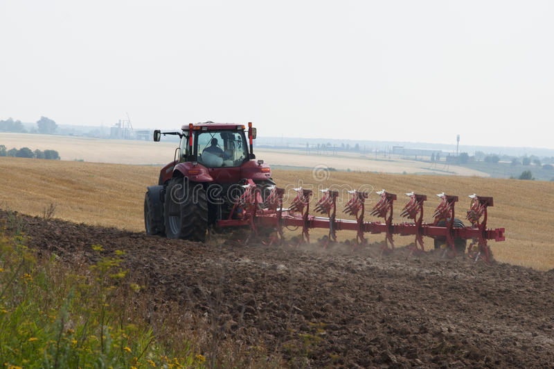 Trator com o arado em processos da terra arável foto de stock