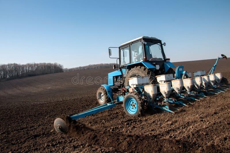 Trator com o sower no campo imagem de stock