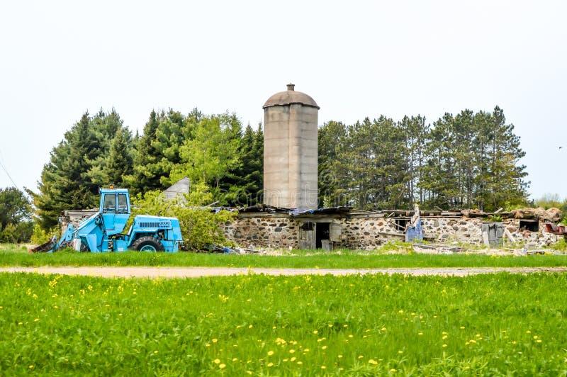 Trator de caso azul na frente de um celeiro destruído fotos de stock