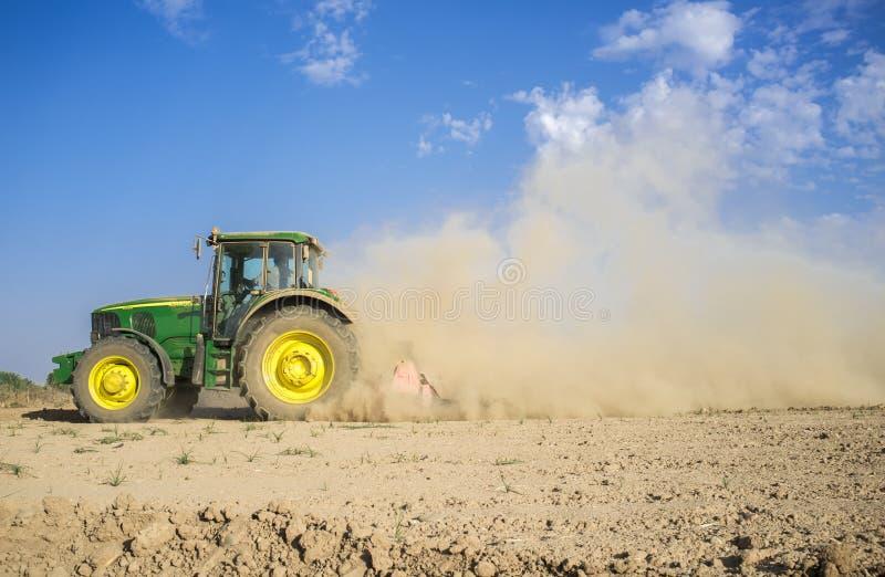Trator de exploração agrícola que prepara o solo empoeirado afetado pela seca foto de stock royalty free