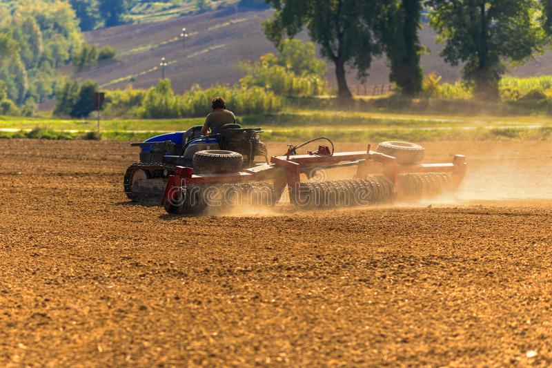 Trator do fazendeiro com o sistema da grade de disco que trabalha em um campo de restolho fotos de stock
