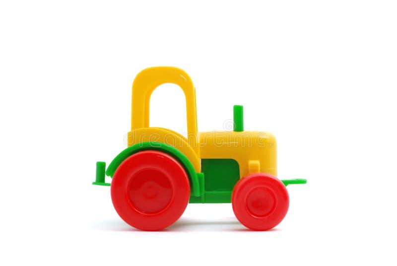 Trator pequeno do brinquedo isolado no branco imagens de stock