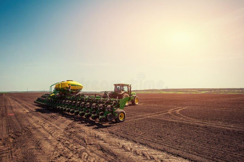 Trator que ara o campo de exploração agrícola à vista da plantação da mola fotos de stock royalty free