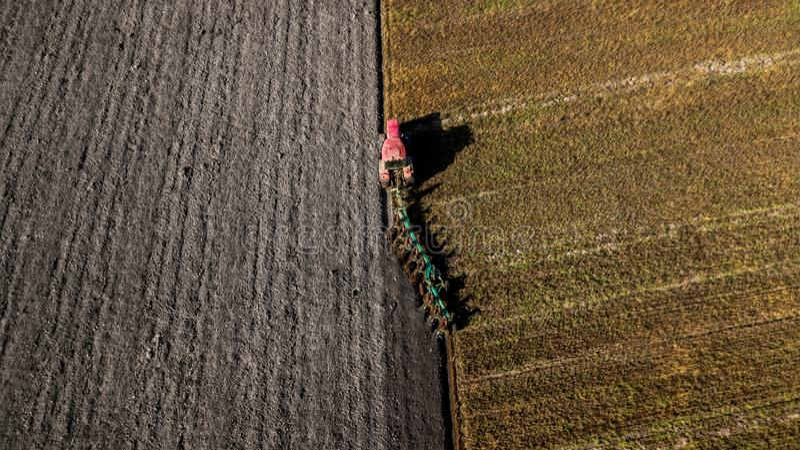 Trator que ara o campo Tiro aéreo Arando campos fotos de stock royalty free