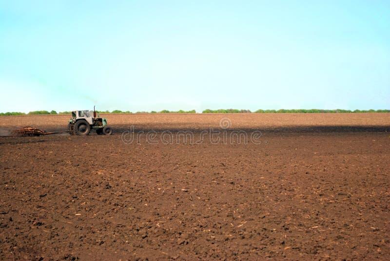 Trator semeia grãos no campo da terra preta, céu azul ensolarado foto de stock