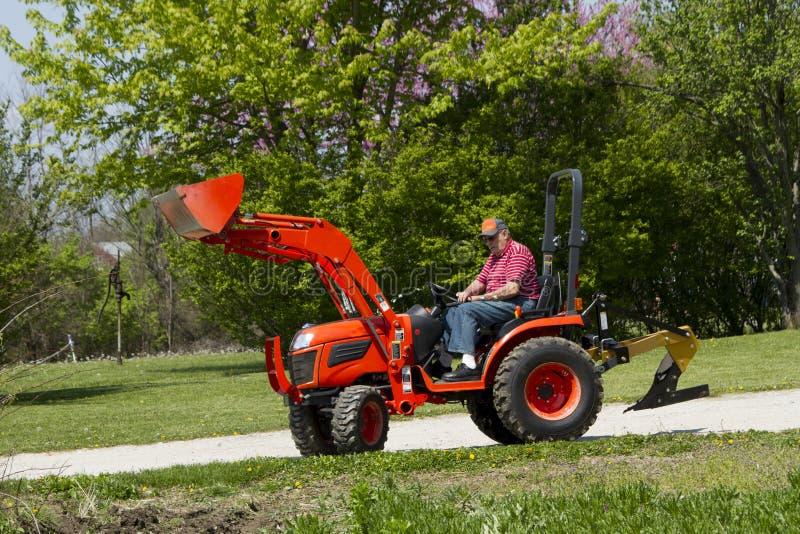 Trator velho de Plowing His Compact do fazendeiro fotos de stock