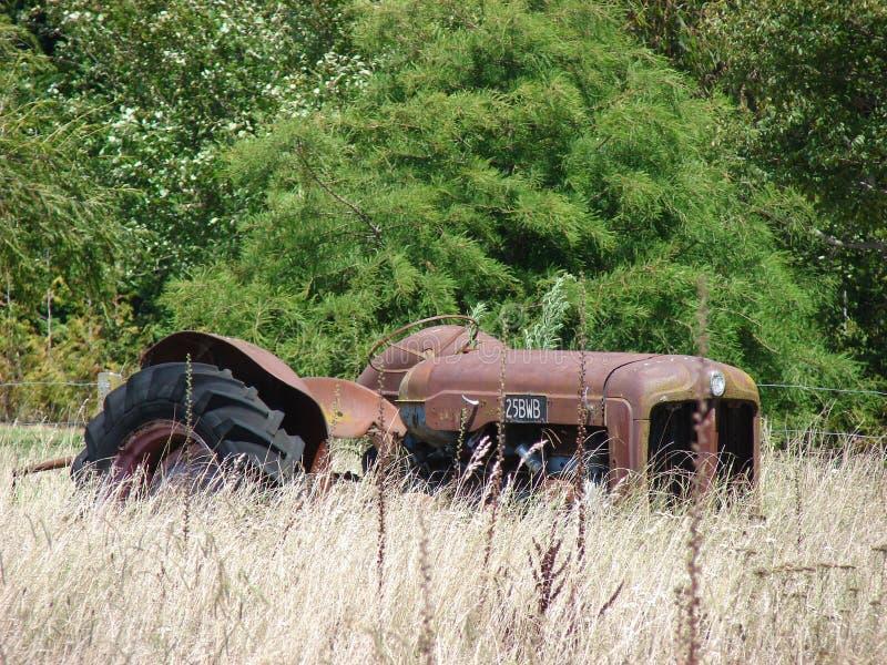 Trator velho na grama seca muito longa imagem de stock
