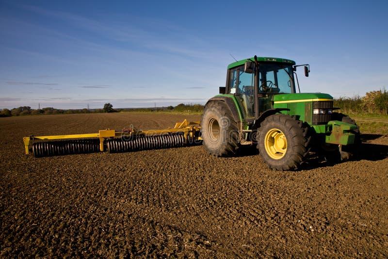 Trator verde com a grade no campo lavrado fotografia de stock royalty free