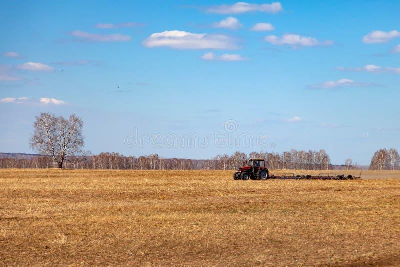 Trator vermelho com um arado arrastado para segar e remover ervas daninhas de campos para a agroind?stria da cor amarela sob o c? foto de stock