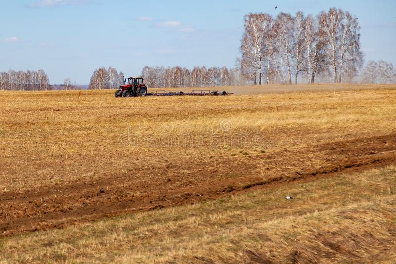 Trator vermelho com um arado arrastado para segar e remover ervas daninhas de campos para a agroind?stria da cor amarela sob o c? imagens de stock