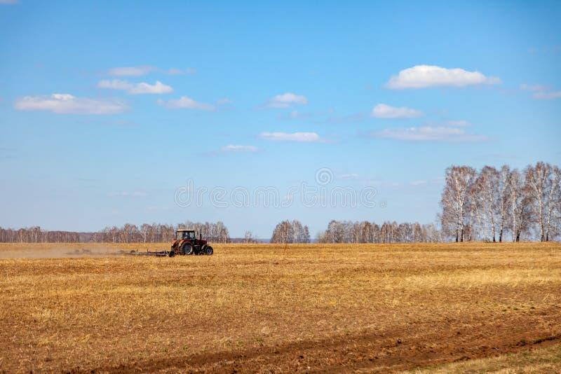 Trator vermelho com um arado arrastado para segar e remover ervas daninhas de campos para a agroind?stria da cor amarela sob o c? fotos de stock royalty free