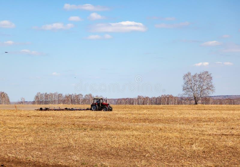 Trator vermelho com um arado arrastado para segar e remover ervas daninhas de campos para a agroind?stria da cor amarela sob o c? imagem de stock