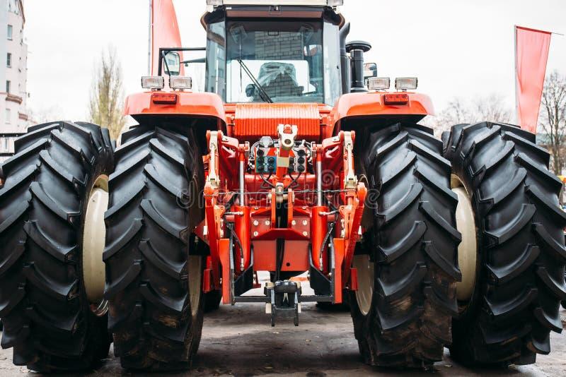 Trator vermelho moderno com rodas grandes, engate hidráulico, quadro de levantamento fotos de stock